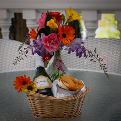 mother's day basket with flowers, champagne and cupcakes